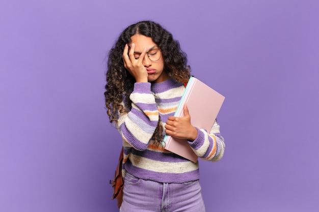 Jonge spaanse vrouw die zich verveeld, gefrustreerd en slaperig voelt na een vermoeiende, saaie en vervelende taak, gezicht met de hand vasthoudend