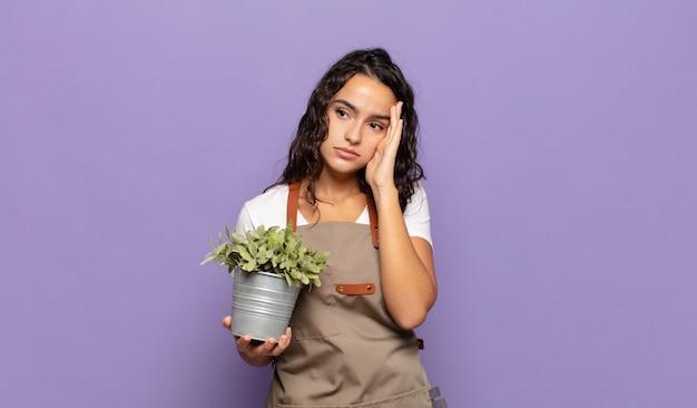 Jonge spaanse vrouw die zich verveeld, gefrustreerd en slaperig voelt na een vermoeiende, saaie en vervelende taak, gezicht met hand vasthoudend