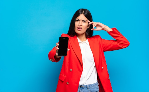 Jonge spaanse vrouw die zich verward en verbaasd voelt en laat zien dat je gek, gek of gek bent. telefoon scherm kopieer ruimte