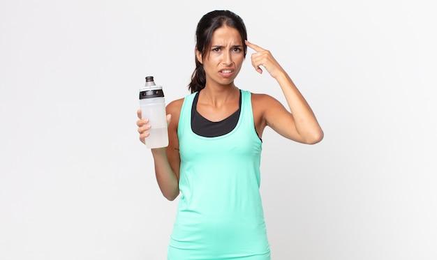 Jonge spaanse vrouw die zich verward en verbaasd voelt, laat zien dat je gek bent en een waterfles vasthoudt. fitnessconcept
