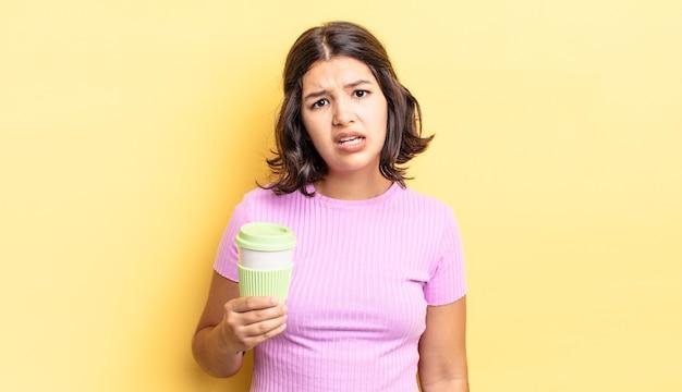 Jonge spaanse vrouw die zich verward en verward voelt. afhaal koffie concept