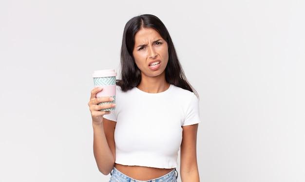 Jonge spaanse vrouw die zich verward en verward voelt en een afhaalkoffiecontainer vasthoudt