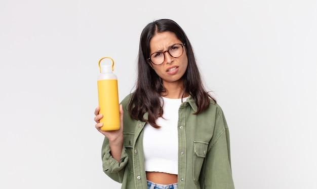 Jonge spaanse vrouw die zich verward en verward voelt en een koffiethermoskan vasthoudt