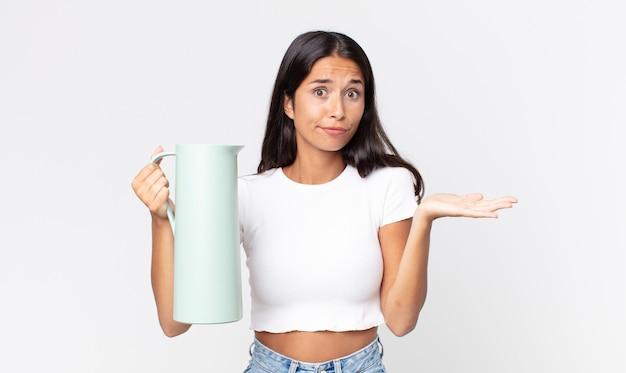 Jonge spaanse vrouw die zich verward en verward voelt en twijfelt en een koffiethermoskan vasthoudt