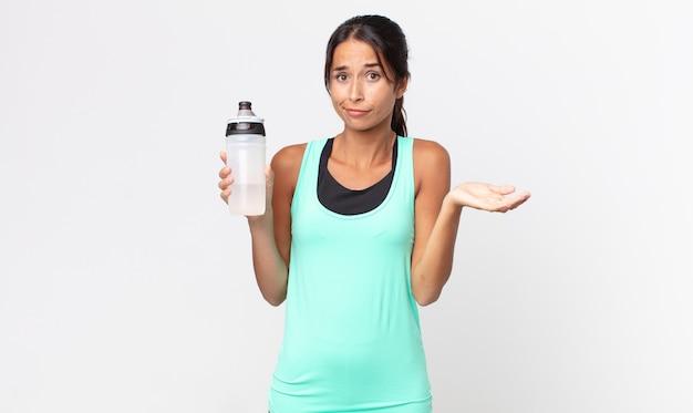 Jonge spaanse vrouw die zich verward en verward voelt en twijfelt en een waterfles vasthoudt. fitnessconcept
