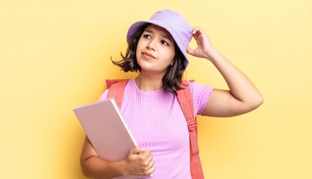 Jonge spaanse vrouw die zich verward en verward voelt, hoofd krabben. terug naar schoolconcept