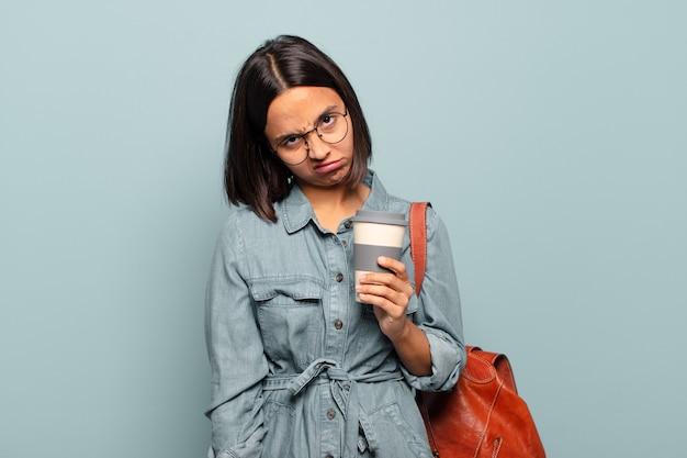 Jonge spaanse vrouw die zich verward en verward voelt, met een stomme, verbijsterde uitdrukking die naar iets onverwachts kijkt