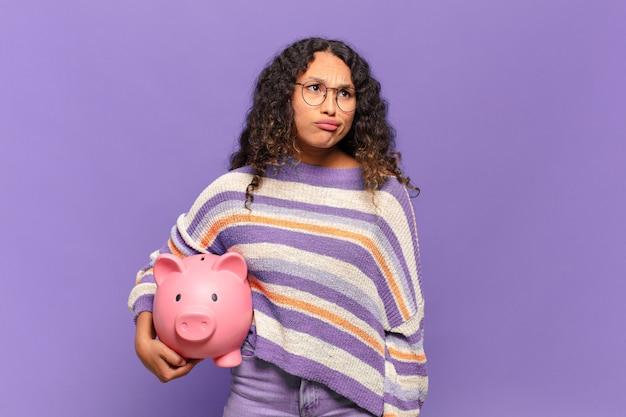 Jonge spaanse vrouw die zich verward en verward voelt, met een stomme, verbijsterde uitdrukking op zoek naar iets onverwachts. spaarvarken concept