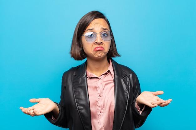 Jonge spaanse vrouw die zich verward en verward voelt, onzeker over het juiste antwoord of de juiste beslissing, probeert een keuze te maken