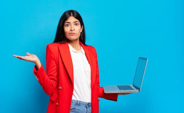 Jonge spaanse vrouw die zich verward en verward voelt, twijfelt, weegt of verschillende opties kiest met grappige uitdrukking. laptopconcept