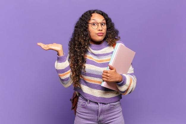Jonge spaanse vrouw die zich verward en verward voelt, twijfelt, weegt of verschillende opties kiest met grappige uitdrukking. studentenconcept