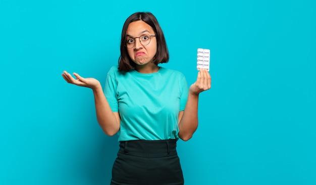 Jonge spaanse vrouw die zich verward en verward voelt, twijfelt, weegt of verschillende opties kiest met grappige uitdrukking