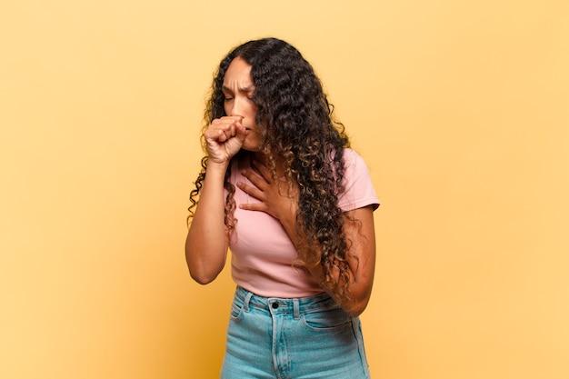 Jonge spaanse vrouw die zich ziek voelt met keelpijn en griepsymptomen, hoesten met bedekte mond