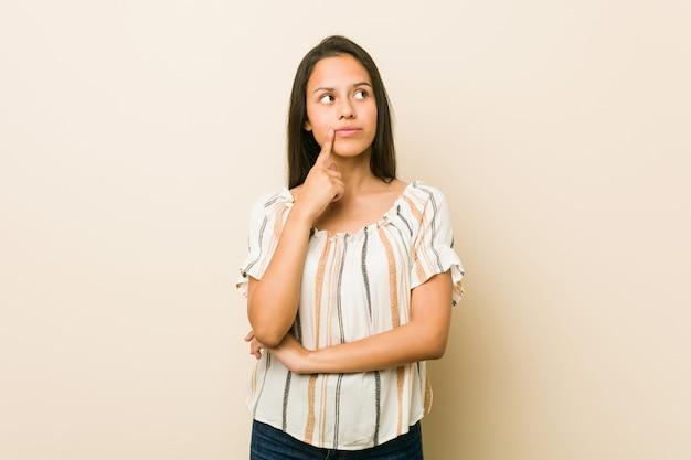 Jonge spaanse vrouw die zijdelings met twijfelachtige en sceptische uitdrukking kijkt.
