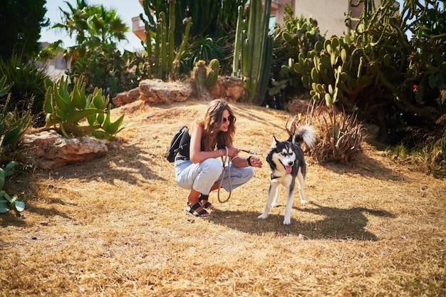Jonge spaanse vrouw gehurkt naast haar siberische husky in park bij zonlicht