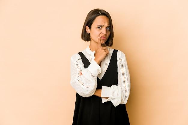 Jonge spaanse vrouw geïsoleerd ongelukkig kijken in de camera met sarcastische uitdrukking.