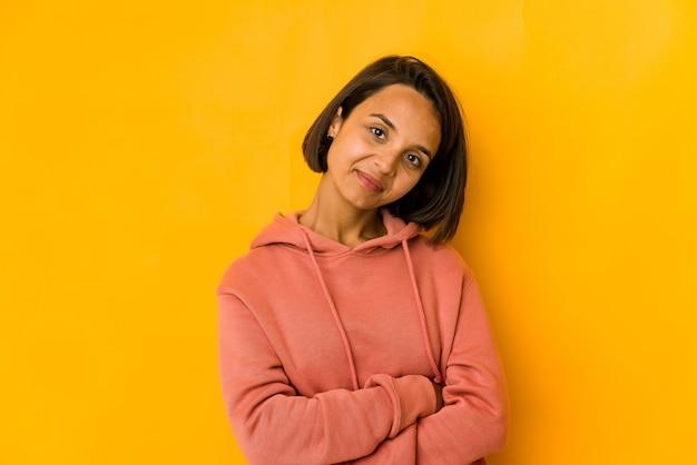 Jonge spaanse vrouw geïsoleerd op geel die zich zelfverzekerd voelt, met vastberadenheid de armen over elkaar steken.