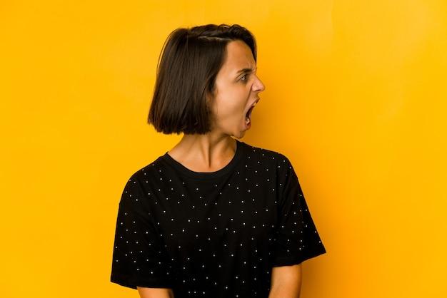 Jonge spaanse vrouw geïsoleerd op geel schreeuwen erg boos, gefrustreerd woedeconcept.