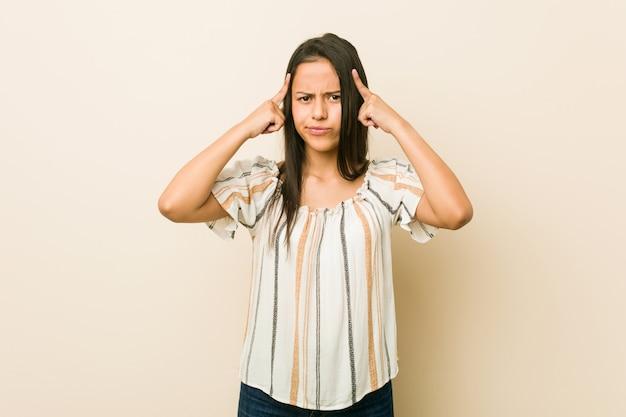 Jonge spaanse vrouw gericht op een taak, wijsvingers hoofd houden.