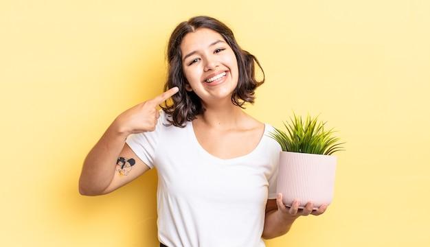 Jonge spaanse vrouw glimlachend vol vertrouwen wijzend naar eigen brede glimlach. groei concept