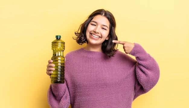 Jonge spaanse vrouw glimlachend vol vertrouwen wijzend naar eigen brede glimlach. olijfolie concept