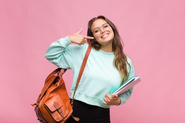 Jonge spaanse vrouw glimlachend vol vertrouwen wijzend op eigen brede glimlach, positieve, ontspannen, tevreden houding