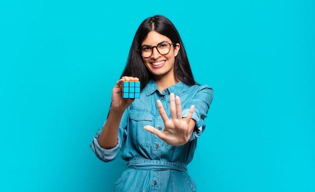 Jonge spaanse vrouw glimlacht en ziet er vriendelijk uit, nummer vijf of vijfde met hand naar voren, aftellend. intelligentie probleem concept