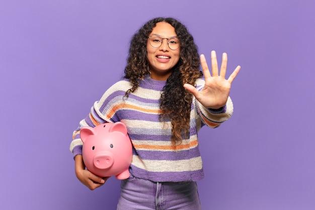 Jonge spaanse vrouw glimlacht en ziet er vriendelijk uit, nummer vijf of vijfde met hand naar voren, aftellend. spaarvarken concept