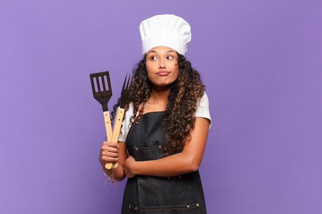 Jonge spaanse vrouw haalt haar schouders op, voelt zich verward en onzeker, twijfelt met gekruiste armen en kijkt verbaasd. barbecue chef-kok concept