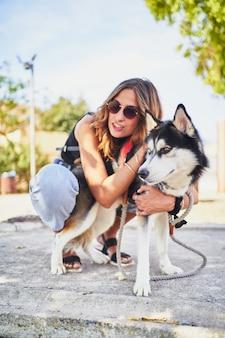 Jonge spaanse vrouw haar siberische husky knuffelen in park