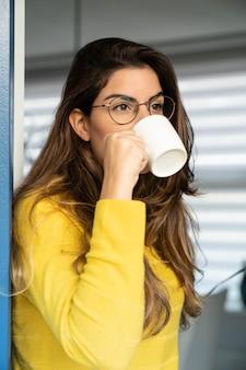 Jonge spaanse vrouw in een geel shirt die koffie drinkt en door het raam kijkt
