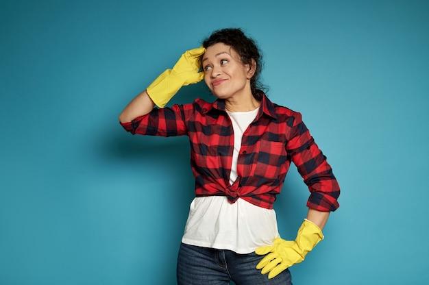 Jonge spaanse vrouw in gele rubberen schoonmaakhandschoenen kijkt ontevreden in de camera