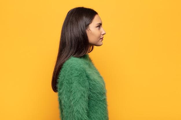 Jonge spaanse vrouw in profielweergave die ruimte vooruit wil kopiëren, denken, fantaseren of dagdromen