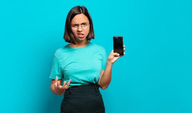 Jonge spaanse vrouw kijkt boos, geïrriteerd en gefrustreerd schreeuwend wtf of wat is er mis met je