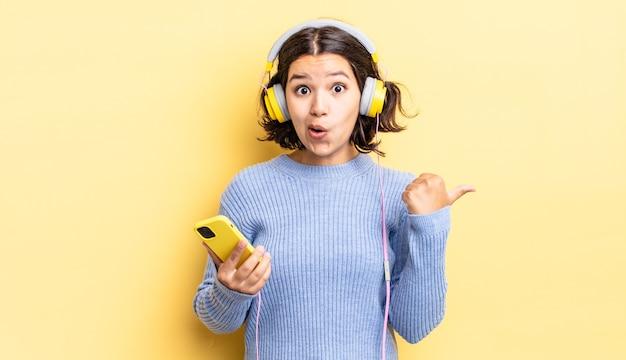 Jonge spaanse vrouw kijkt verbaasd in ongeloof. koptelefoon en smartphone concept