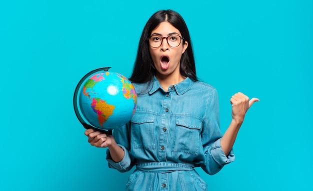 Jonge spaanse vrouw kijkt verbaasd van ongeloof, wijst naar een voorwerp op de zijkant en zegt wow, ongelooflijk. aarde planeet concept