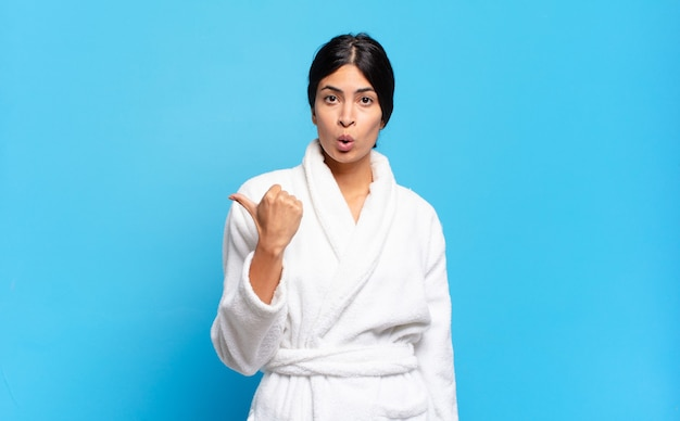 Jonge spaanse vrouw kijkt verbaasd van ongeloof, wijst naar een voorwerp op de zijkant en zegt wow, ongelooflijk. badjas concept