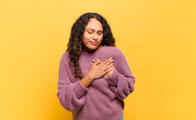 Jonge spaanse vrouw kijkt verdrietig, gekwetst en diepbedroefd, houdt beide handen dicht bij het hart, huilt en voelt zich depressief