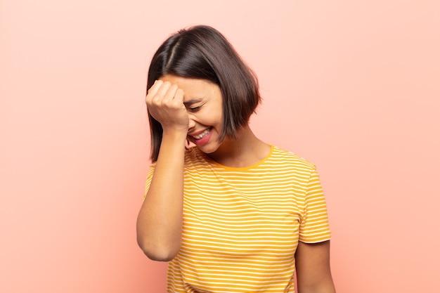 Jonge spaanse vrouw lacht en slaat op het voorhoofd alsof ze dã€â™oh! ik was het vergeten of dat was een stomme fout