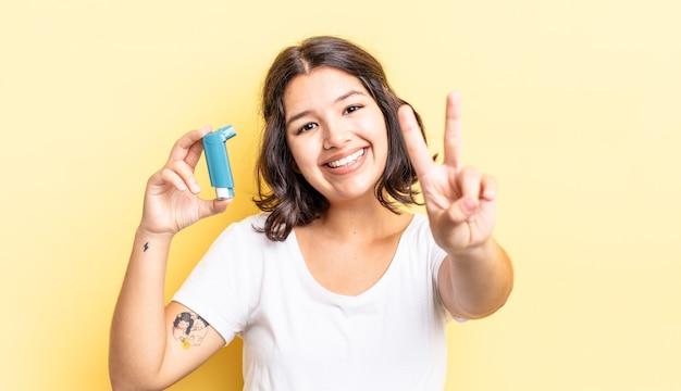 Jonge spaanse vrouw lacht en ziet er gelukkig uit, gebarend overwinning of vrede. astma concept