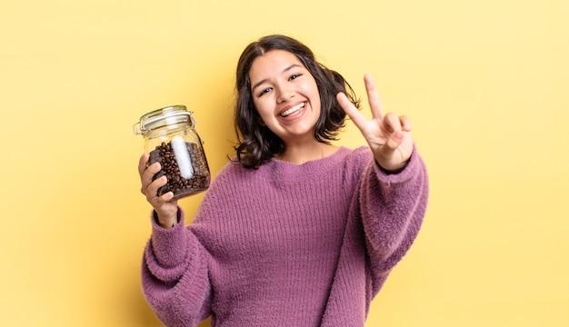 Jonge spaanse vrouw lacht en ziet er gelukkig uit, gebarend overwinning of vrede. koffiebonen concept
