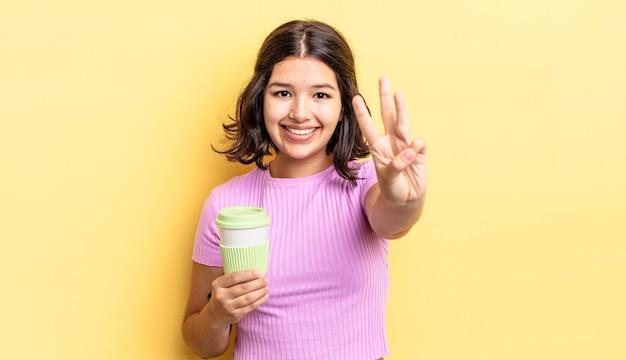 Jonge spaanse vrouw lacht en ziet er vriendelijk uit, met nummer drie. afhaal koffie concept