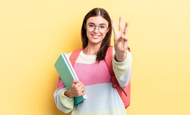 Jonge spaanse vrouw lacht en ziet er vriendelijk uit, met nummer drie. studentenconcept