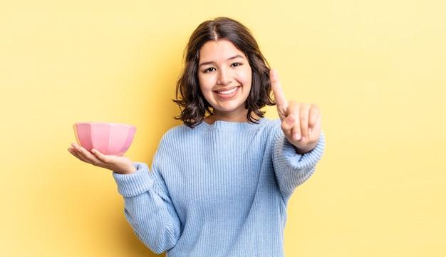 Jonge spaanse vrouw lacht en ziet er vriendelijk uit, met nummer één. lege kom concept