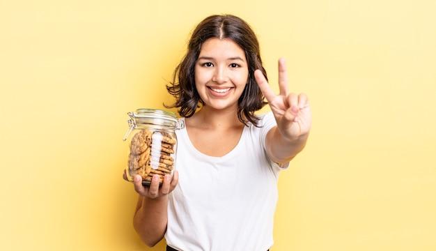 Jonge spaanse vrouw lacht en ziet er vriendelijk uit, met nummer twee. koekjes fles concept