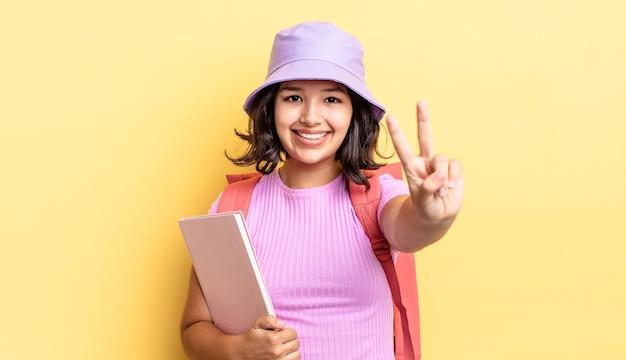 Jonge spaanse vrouw lacht en ziet er vriendelijk uit, met nummer twee. terug naar schoolconcept
