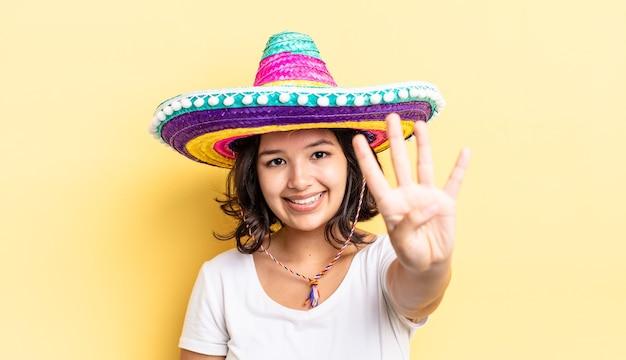 Jonge spaanse vrouw lacht en ziet er vriendelijk uit, met nummer vier. mexicaanse hoed concept