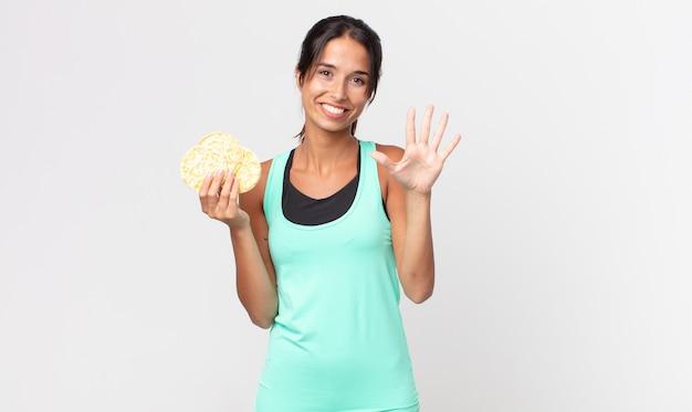 Jonge spaanse vrouw lacht en ziet er vriendelijk uit, met nummer vijf. fitness dieet concept