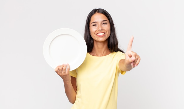 Jonge spaanse vrouw lacht en ziet er vriendelijk uit, toont nummer één en houdt een leeg bord vast