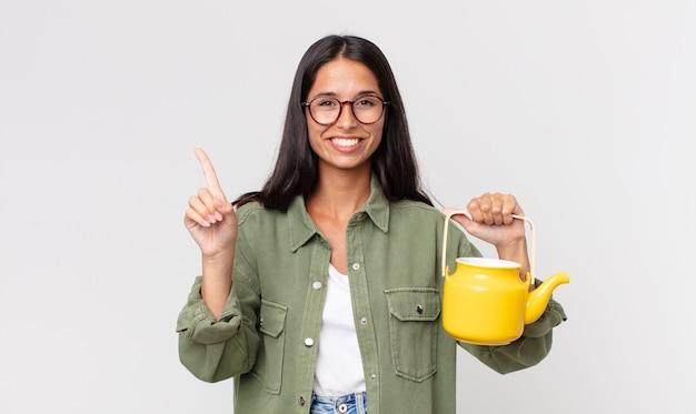 Jonge spaanse vrouw lacht en ziet er vriendelijk uit, toont nummer één en houdt een theepot vast